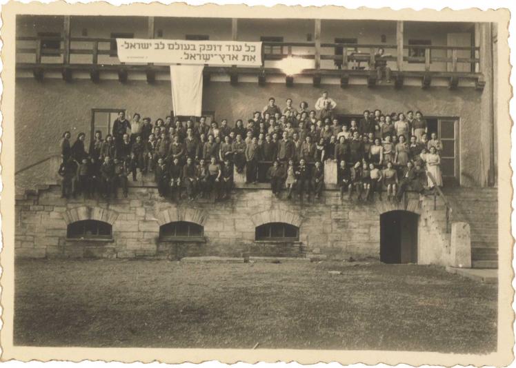 Auf der Schwarz-Weiß-Fotografie sitzen circa 100 Frauen und Männer auf einer Veranda. Über ihnen hängt ein Banner mit einem hebräischen Zitat aus einem Lied von Pooa Grinshpon.