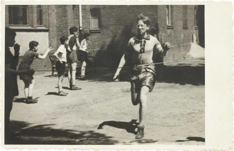 Im Bildvordergrund ist ein rennender Junge zu sehen, der im Begriff ist, die Ziellinie zu erreichen, im Bildhintergrund zuschauende Jungs (Schwarz-Weiß-Foto)