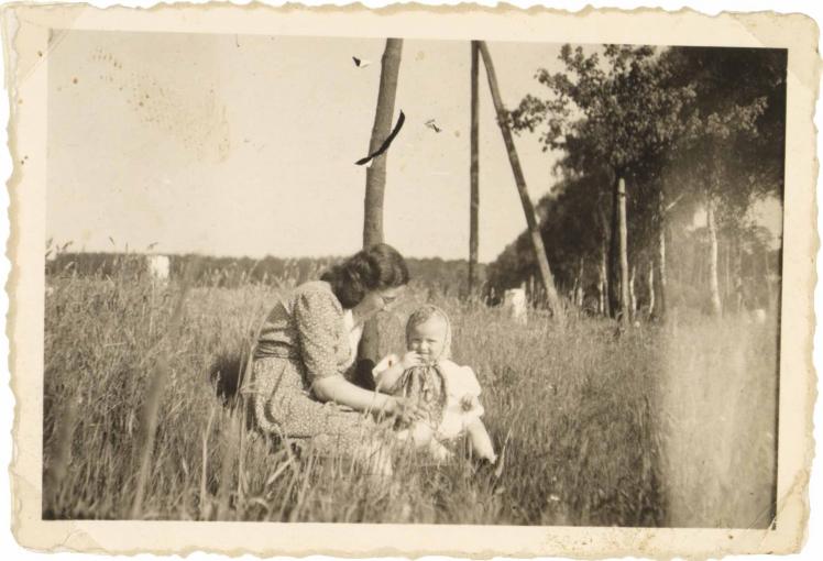 Die Frau trägt ein mittelhelles, gemustertes Kleid sowie eine Brille. Das Kind sitzt rechts neben ihr. Es trägt ein helles Kleid und ein mittehelles gemustertes Kopftuch (Schwarz-Weiß-Fotografie)