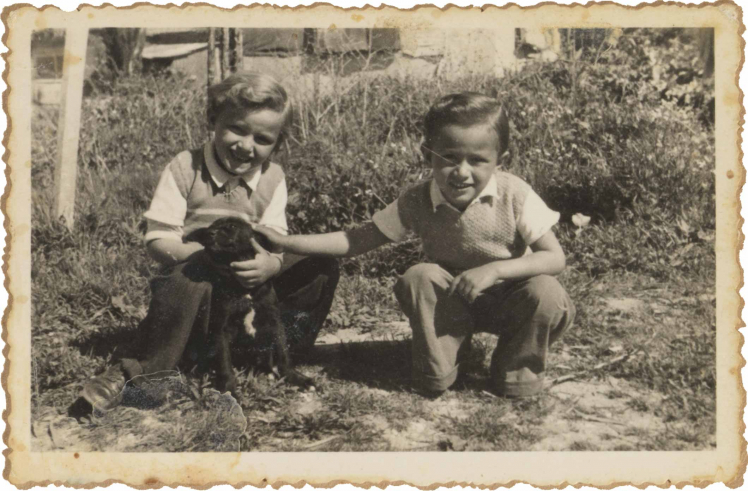 On the black-and-white picture, the two children squat in a garden with a puppy.