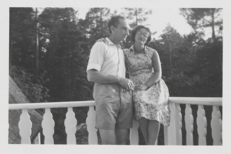 In the black-and-white photo, Leonie is sitting in a summer dress on the rail of a balcony. Walter stands next to her with his left arm around her and holding a cigarette in his right hand.