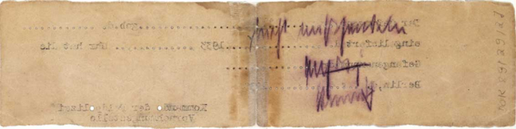 Back of a long, yellowed slip of paper with a handwritten note and a few inverted, typed letters pressed through from the front.