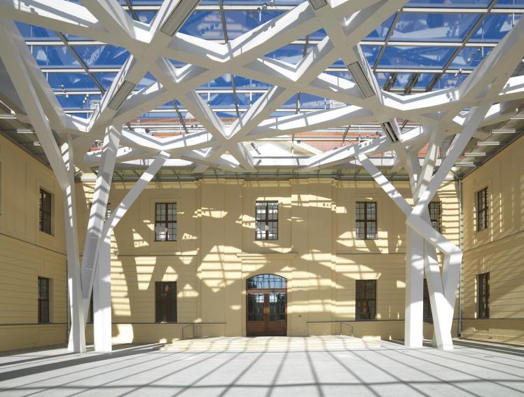 Innenansicht des Glashofs des Jüdischen Museums Berlin; die Dachfenster werfen Schatten auf den Boden