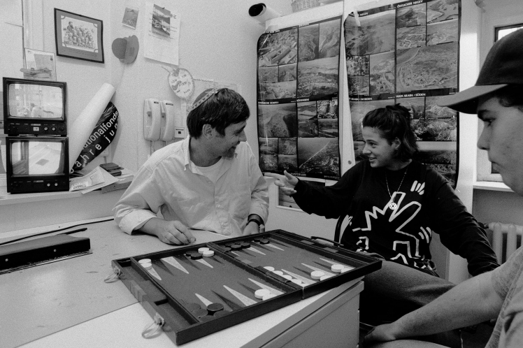 Black and white photography: a man with kippa is playing Backgammon with two kids