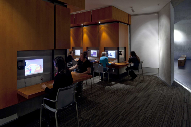 Interior view of the Rafael Roth Learning Center in the basement of the Jewish Museum Berlin. Several people are looking at screens.