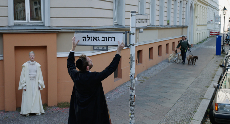 A man wearing a kippah mounts a street sign with a Hebrew street name. To his left, a woman in white robes stands in the frame of a bricked-up door that is part of the orange pedestal of a renovated old building, watching him