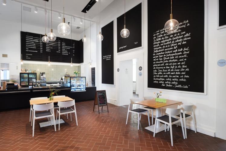 Museumscafé mit Theke, Tischen und Speisetafeln