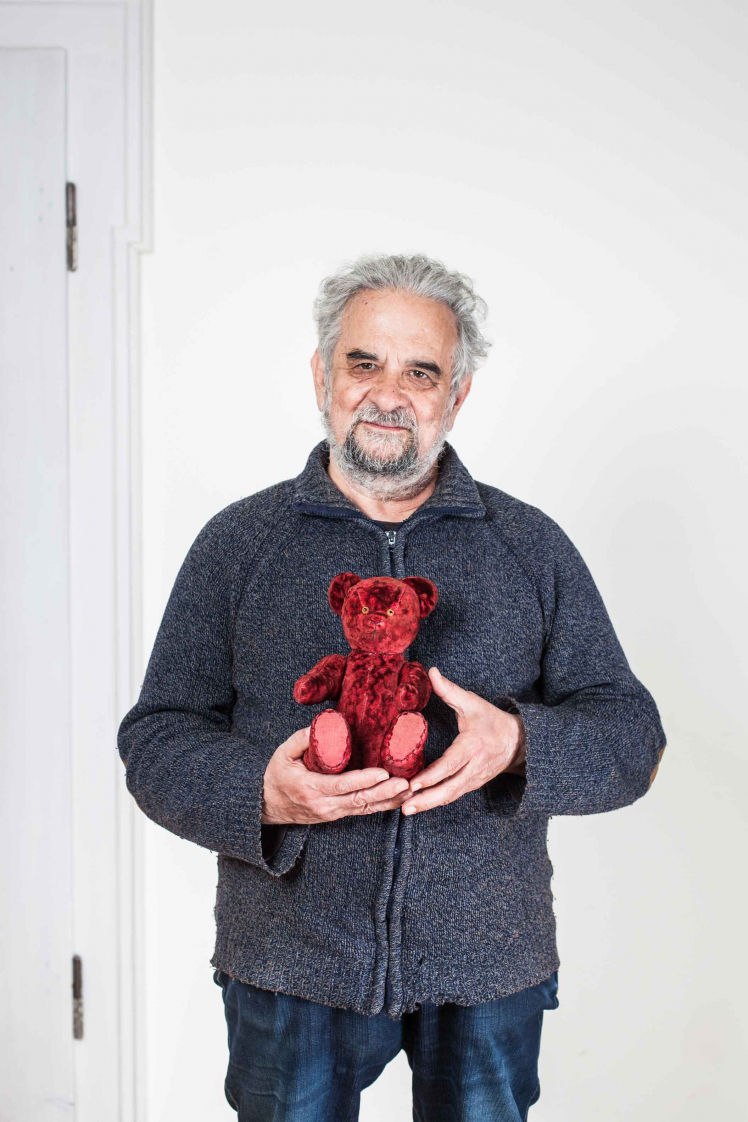 Elderly man holding a red teddy bear in his hands