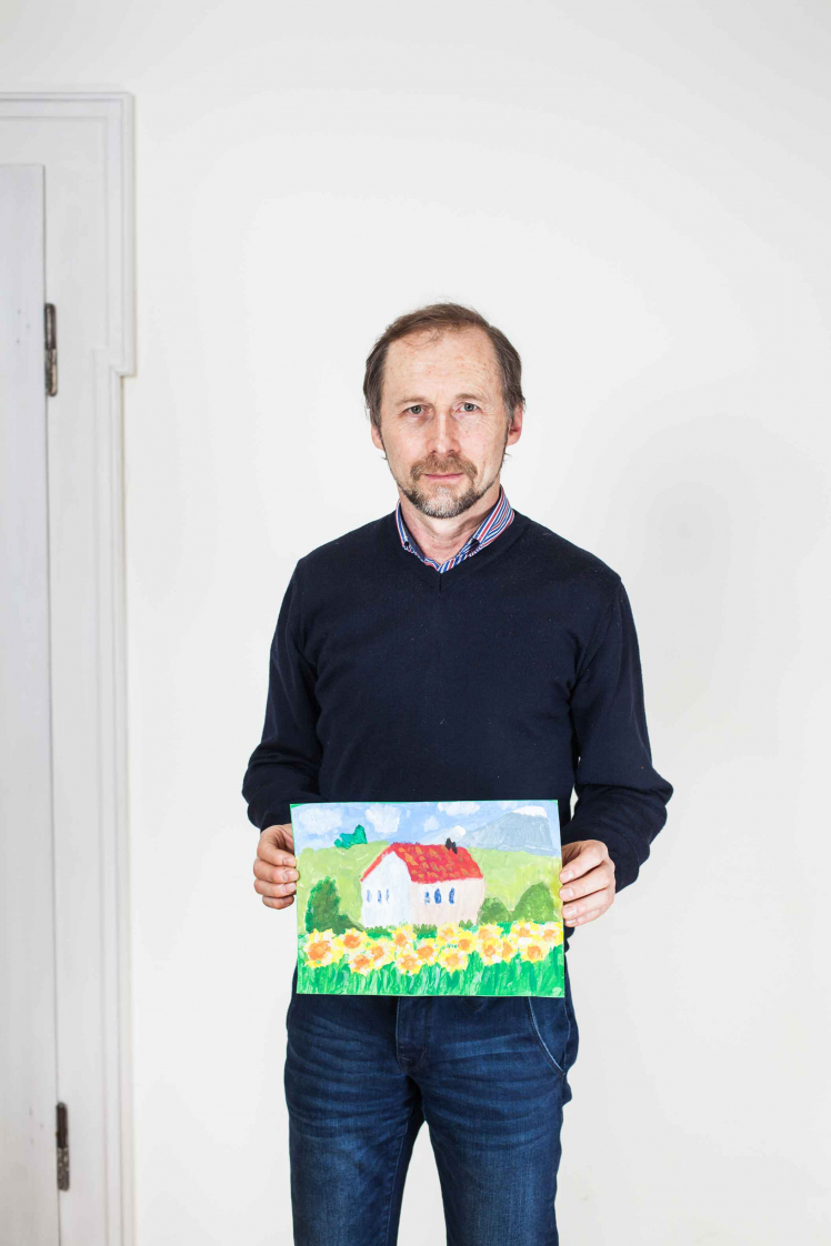 A middle-aged man is holding a colourful picture, hand-painted by his daughter; the picture shows a little house and a flower