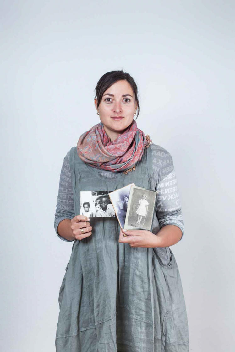 A young woman holding black and white photographs in her hand