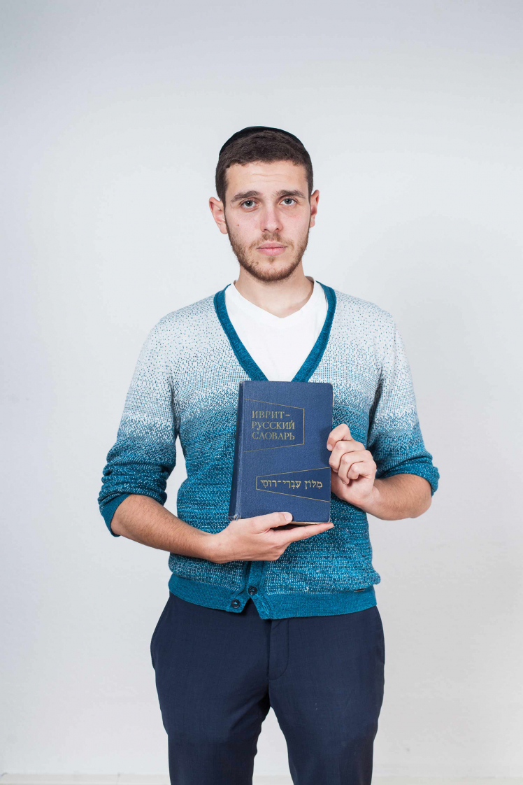 a young man holding a blue Russian-Hebrew dictionary.