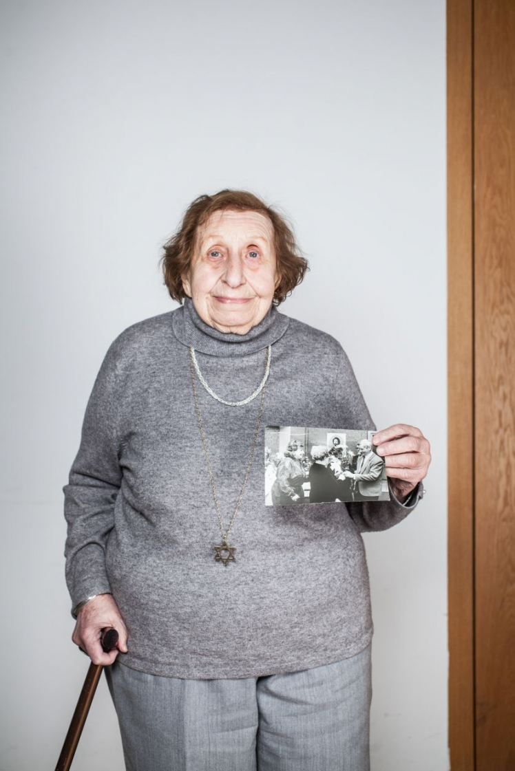 A woman leans on a cane and holds two photos in her hand.