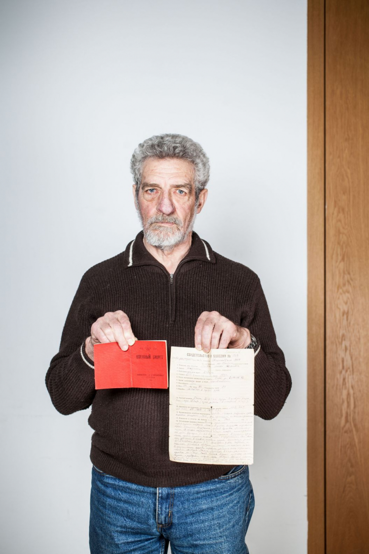 A bearded gray-haired man holds up two documents