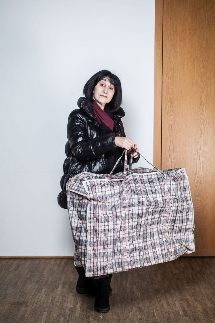 A woman in a thick winter jacket wears a huge plaid bag.