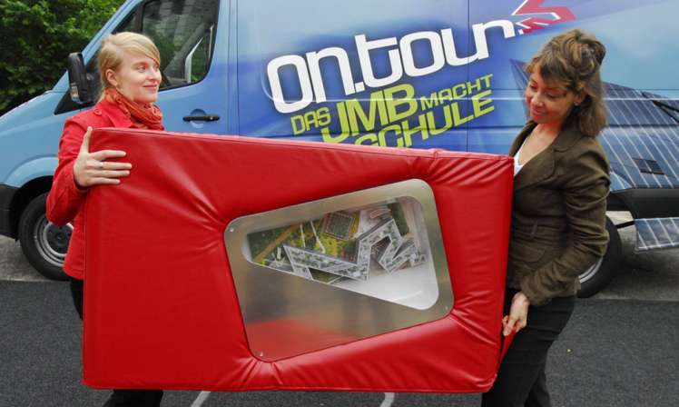 Two employees from ontour carry a red cube seat containing a model of the Jewish Museum's Libeskind building.