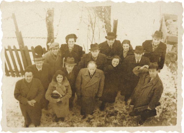 Ausgewaschenes Schwarz-Weiß-Foto einer Gruppe von 14 Männern und Frauen in Mänteln. Sie stehen auf einer schneebedeckten Fläche vor einem Zaun und wurden von oben fotografiert. Fast jeder schaut in die Kamera, einige lächeln.