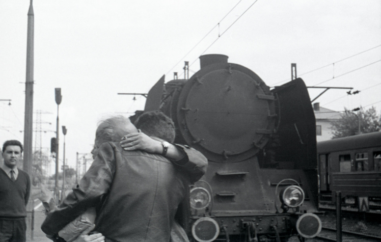 Two men hug at a train station