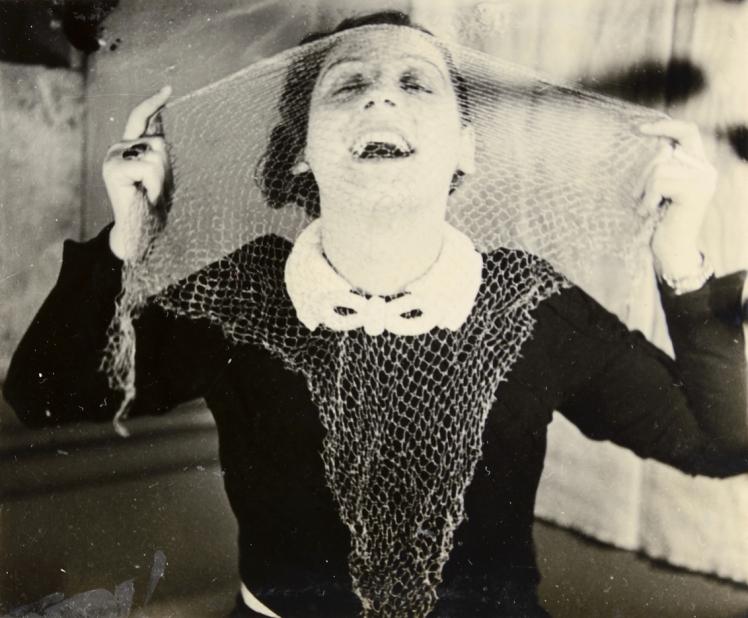 Porträt einer Frau, die sich Spitzenstoff vor ihr Gesicht hält