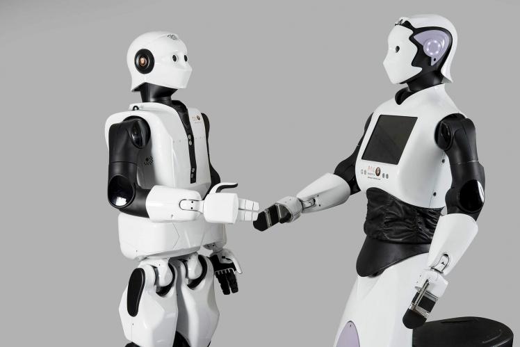 Zwei Roboter, die sich die Hand reichen
