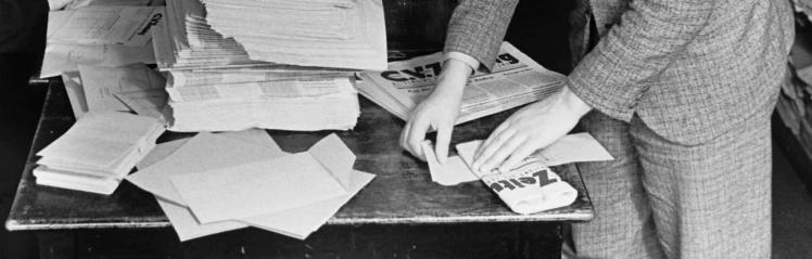 Schwarz-Weiß-Fotografie: Das Bild zeigt Hände, die Zeitungen für den Versand kuvertieren