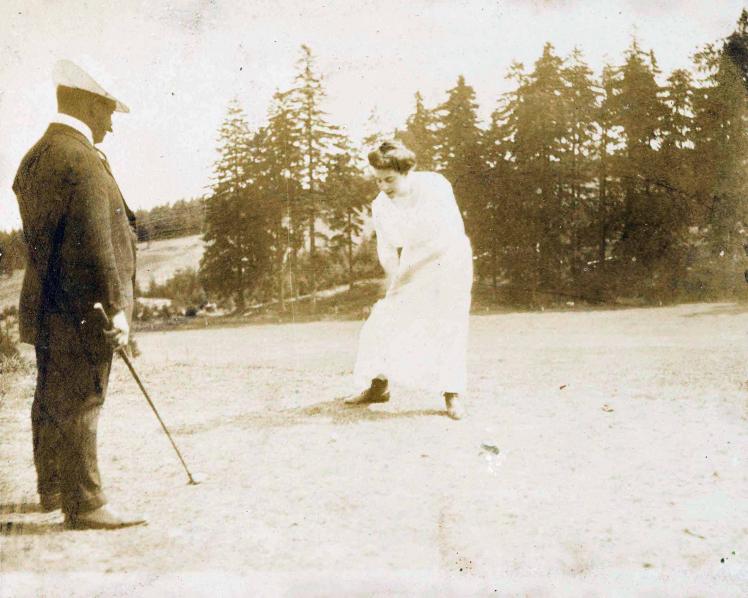 Links im Bild ist ein Mann im Anzug mit Golfschläger zu sehen, in der Mitte eine Frau in weißem Kleid, die sich anschickt, einen Golfball zu schlagen.