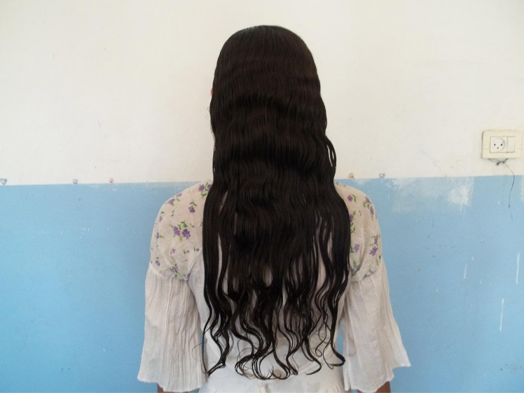 Foto einer Frau von hinten, vom Kopf bis zur Hüfte, mit langen dunklen Haaren vor blau-weißer Wand