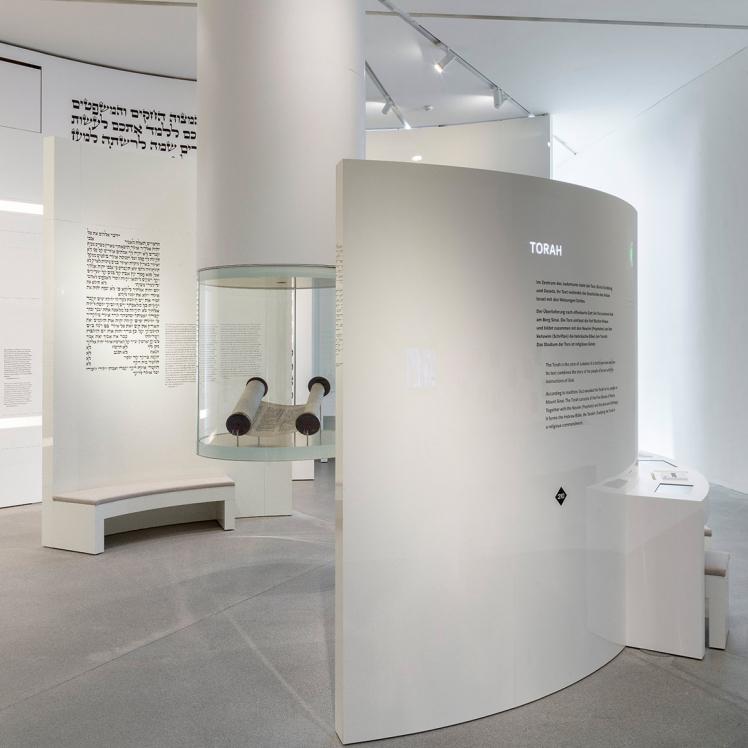 Von der Decke hängende runde Vitrine mit einer Tora-Rolle darin, an einer Wand dahinter die zehn Gebote auf Hebräisch, darum halbrunde weiße Ausstellungswände mit Text
