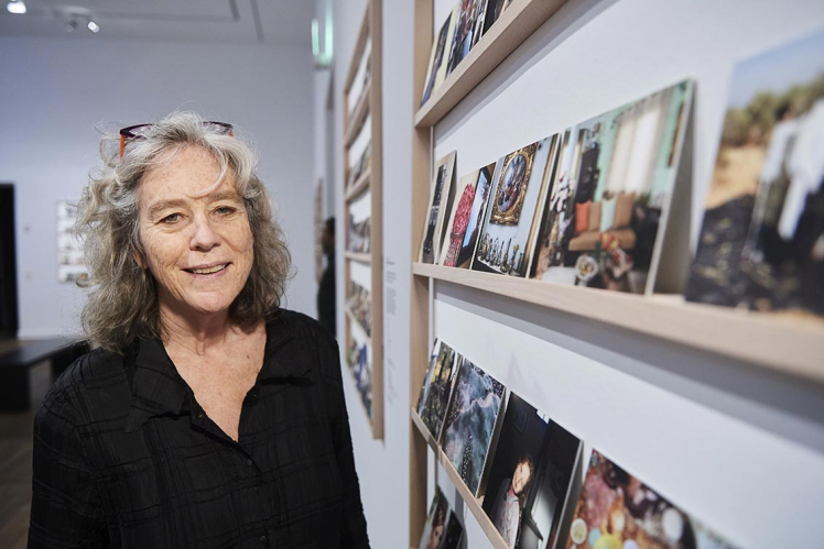 Wendy Ewald stands next to a shelf with photographs