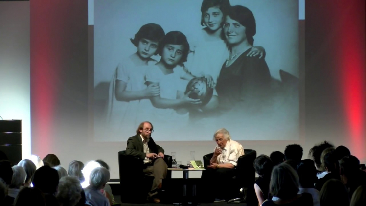Anita Lasker Wallfisch (right) and Aubrey Pomerance (left) sit on a podium in front of an audience. In the background: projection of a family photo