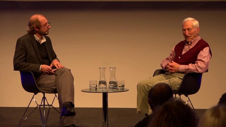 An einem Tisch sitzen zwei Männer im Gespräch an einem niedrigen Couchtisch: rechts Kurt Roberg, links Aubrey Pomerance
