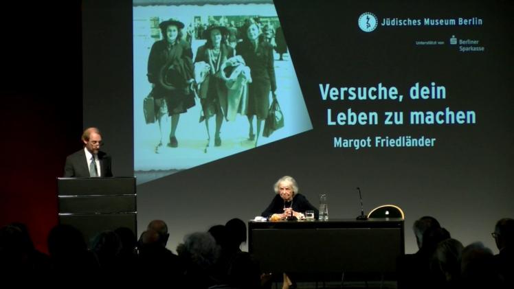 Auf einem Podium steht links im Bild Aubrey Pomerance an einem Stehpult, rechts im Bild sitzt Margot Friedländer an einem Tisch