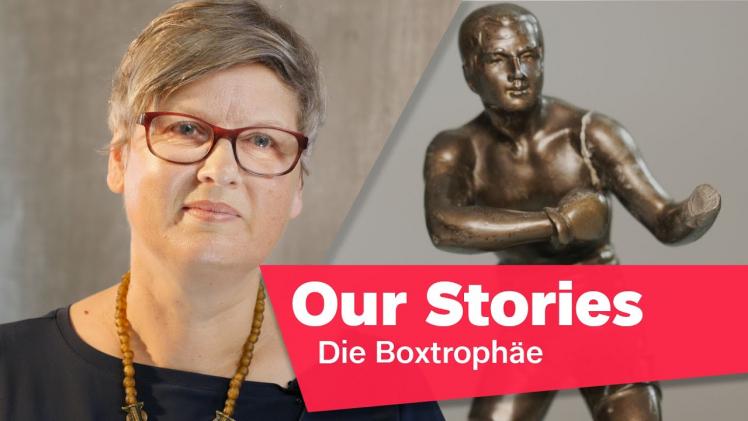 """Porträtfoto von Leonore Maier, im Hintergrund eine beschädigte Statue eines Boxers, rechts unten im Bild der Schriftzug """"Our Stories: Die Boxtrophäe"""""""
