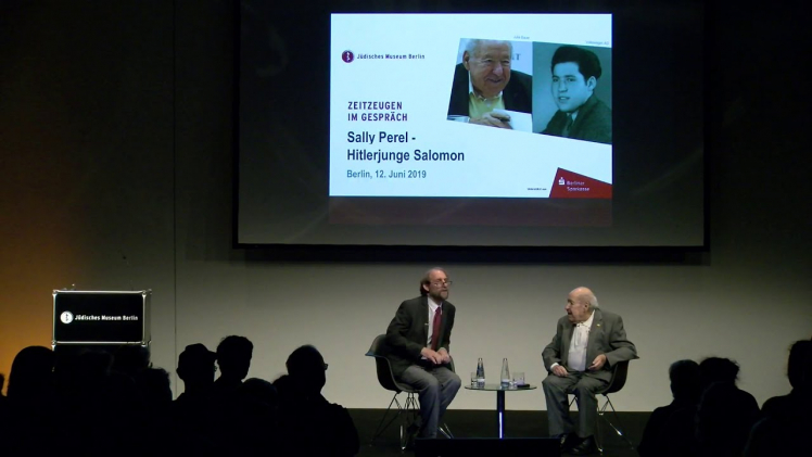 An einem Tisch sitzen zwei Männer im Gespräch an einem niedrigen Couchtisch: rechts Sally Perel, links Aubrey Pomerance