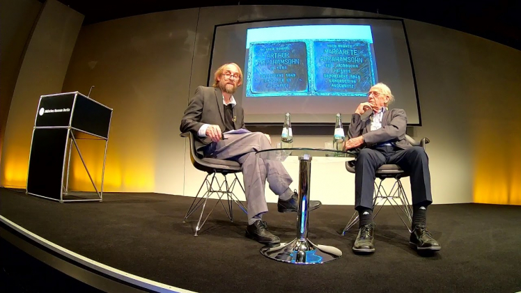 Two men sit talking at a low coffee table: Zvi Aviram on the right, Aubrey Pomerance on the left