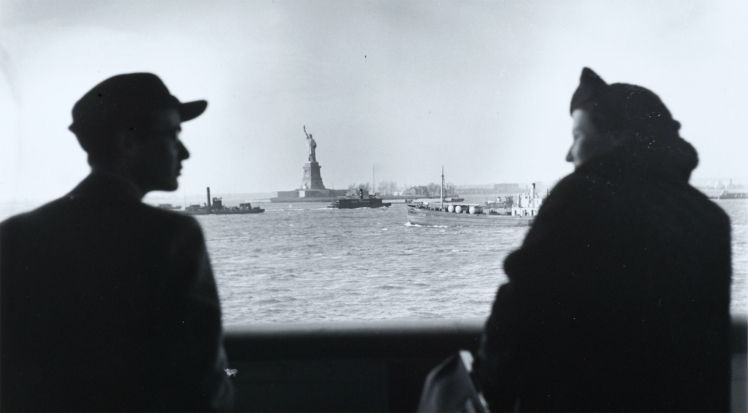 A man and a woman looking at each other, in semi-profile, on a ship, with a clear view over the water to the Statue of Liberty