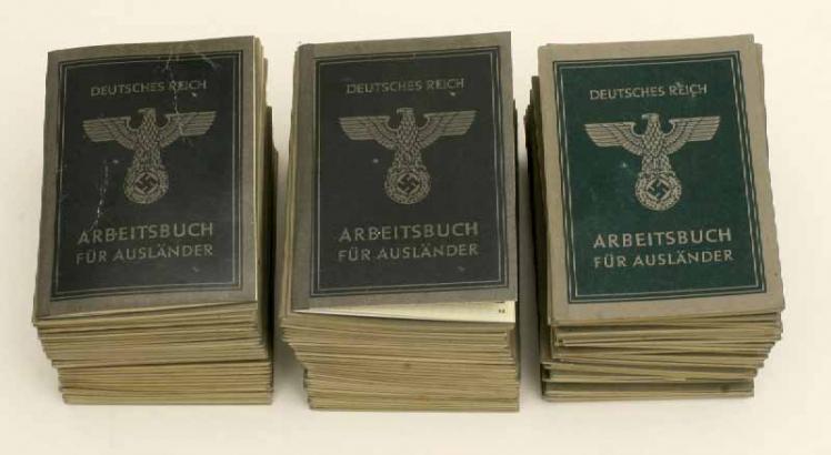 Drei Stapel Arbeitsbücher mit Reichsadler, Hakenkreuz und der Beschriftung »Deutsches Reich, Arbeitsbuch für Ausländer«