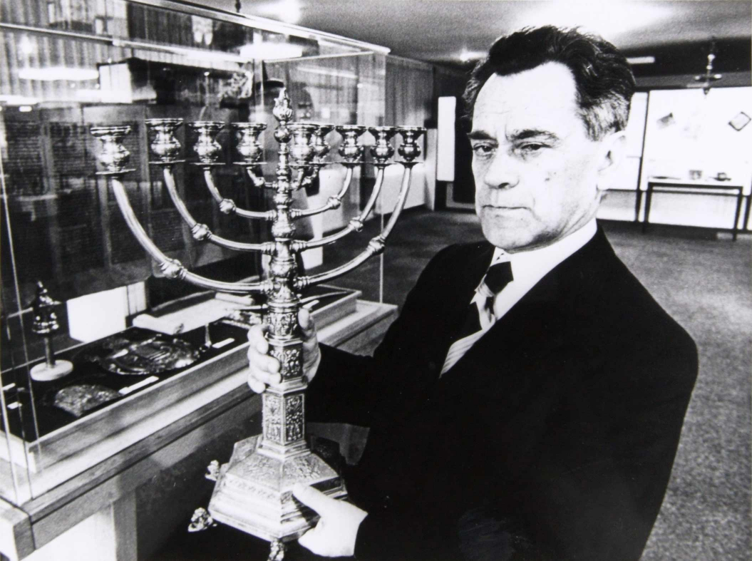 Schwarz-weiß-Foto eines Mannes im Anzug, der einen großen Chanukka-Leuchter hält