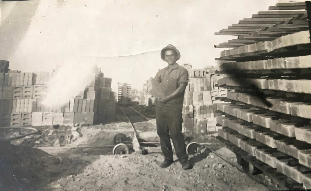 Black-and-white photo of a young man in a hat with bricks in his arms; more bricks in the background