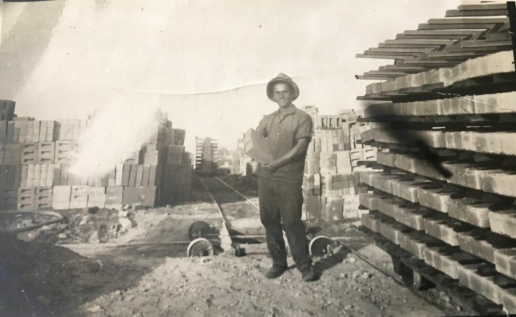 Schwarz-weiß-Foto eines jungen Mannes mit Hut, der Ziegelsteine im Arm hält, im Hintergrund ebenfalls Ziegelsteine