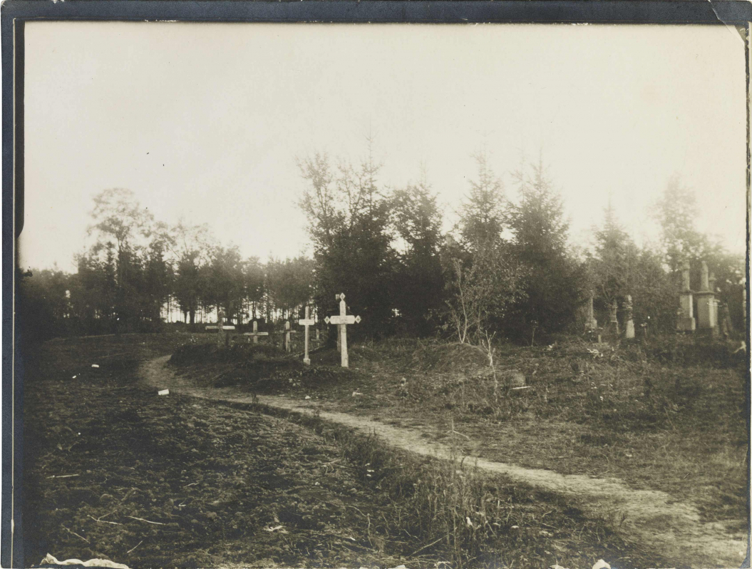 Black-and-white photograph: Graves with crosses near a sandy path, with more graves and a forest in the background