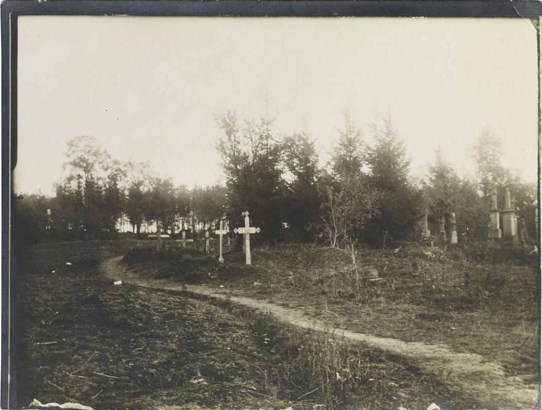 Schwarz-weiß-Foto: Gräber mit Grabkreuzen, neben einem Sandweg, im Hintergrund weitere Grabsteine und ein Wäldchen