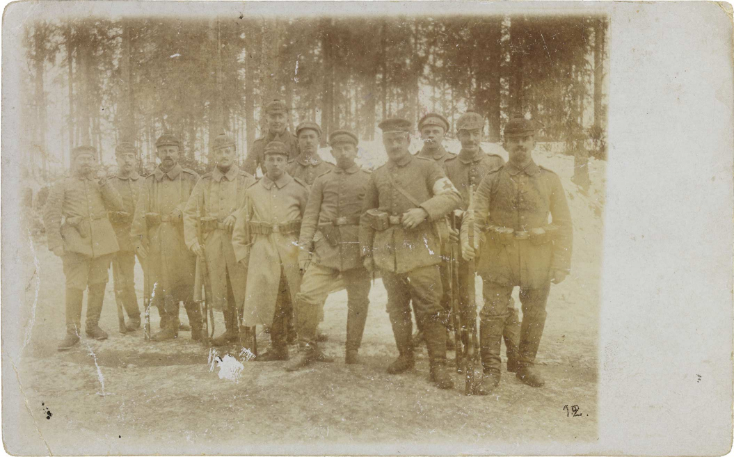 Black-and-white photograph: twelve uniformed soldiers in a snowy pine forest