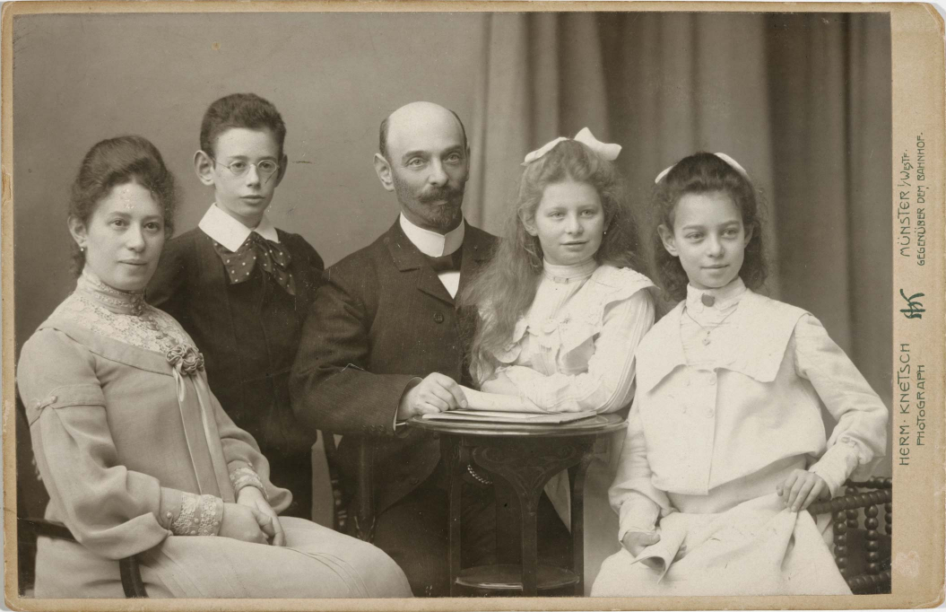 Black-and-white studio photograph: couple with two daughters and a son