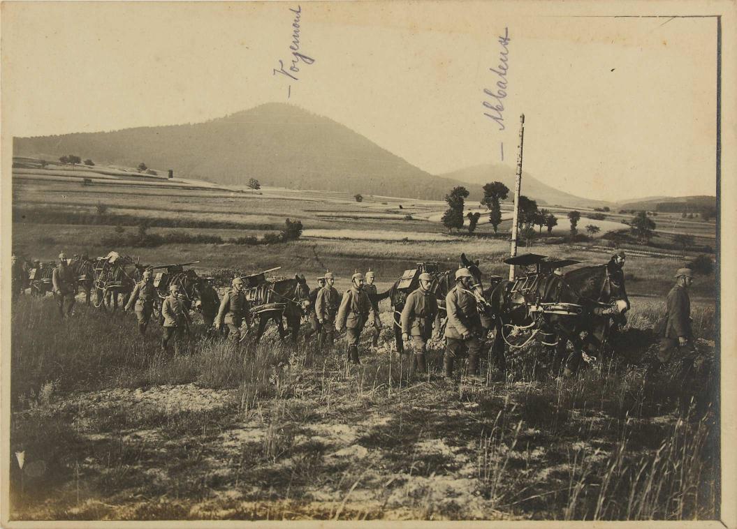 Schwarz-weiß-Foto: Ein Tross Soldaten mit Eseln, durch eine Ebene marschierend, im Hintergrund Berghügel
