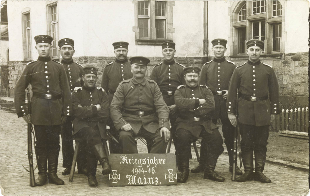 Black-and-white photograph: nine uniformed soldiers in front of a barracks
