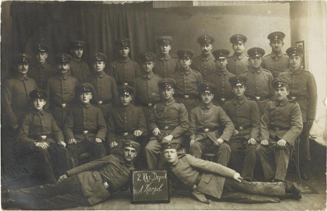 Black-and-white studio photograph: twenty-four soldiers in uniform