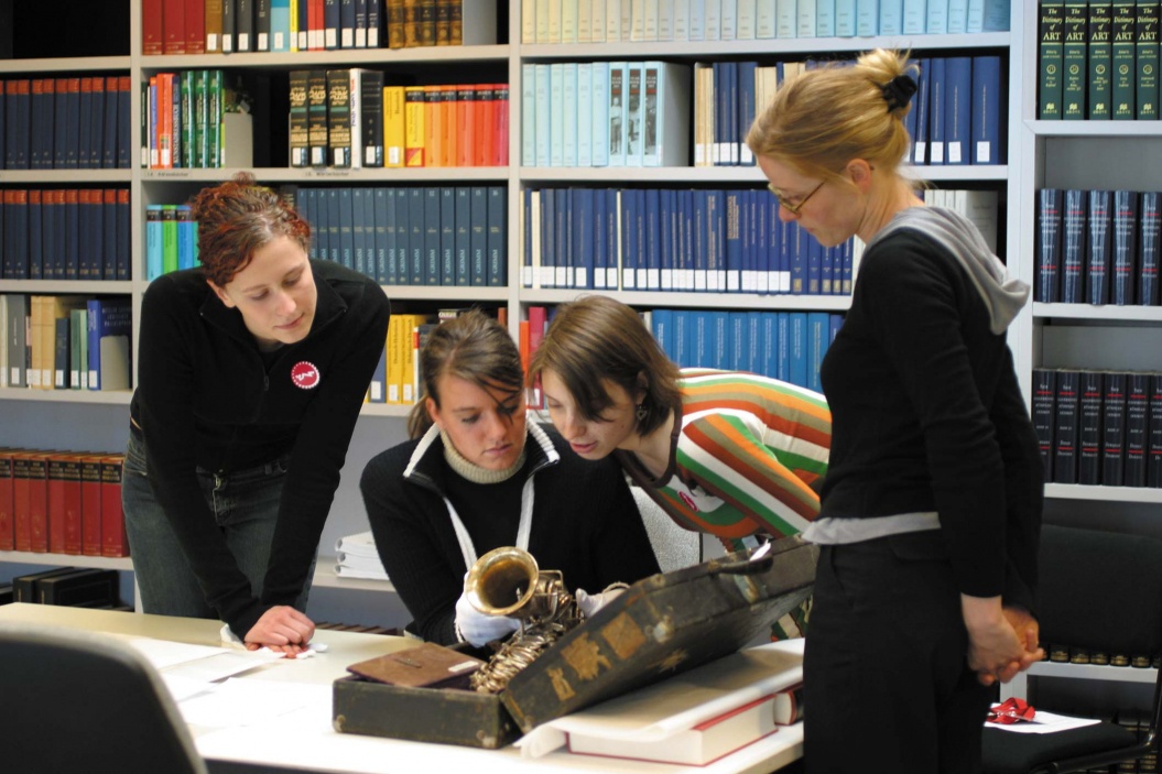 drei Mädchen und eine Mitarbeiterin des Jüdischen Museums betrachten ein altes Saxophon