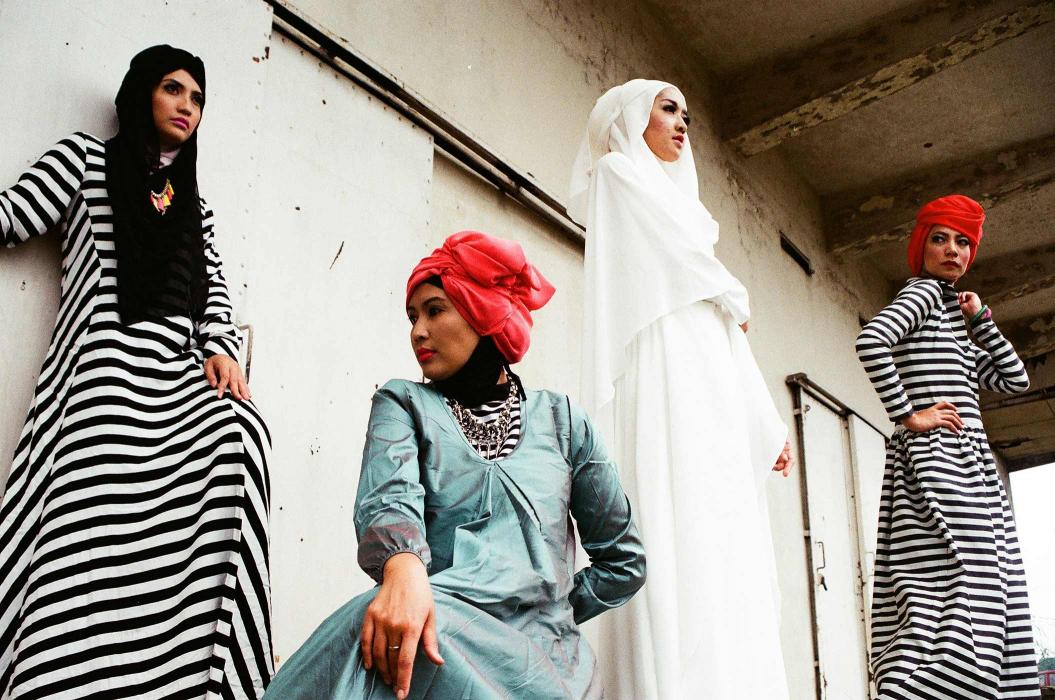 Vier Frauen in langen Kleidern und Hijabs