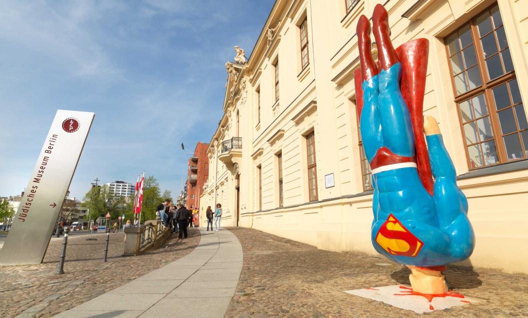 Skulptur, die Superman zeigt, wie er aus senkrechtem Flug auf dem Boden aufprallt