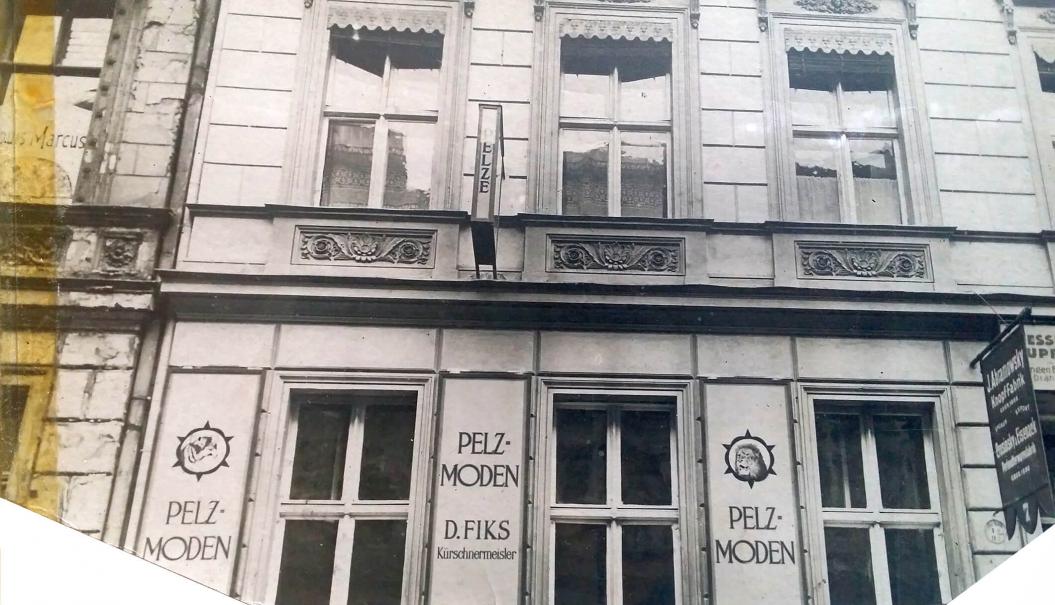 schwarz-weiß-Foto: Fassade eines Wohnhauses mit Werbung zwischen den Fenstern
